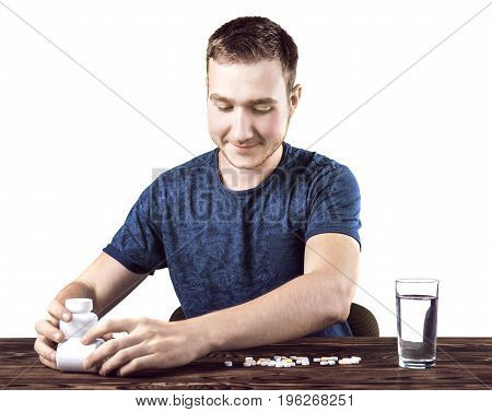 A smiling guy looking at various tablets and drugs isolated over the white background. A cheerful male taking prescripted medicaments. An ill young man sitting next to the brown wooden table.