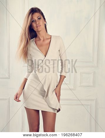 Beautiful Woman With Long Hair Standing And Posing In Fashion Elegant White Dress On Light Wall Back