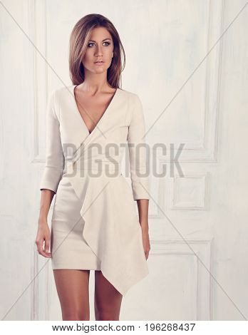 Beautiful Woman With Long Hair Standing And Posing In Fashion White Elegant Dress On Light Wall Back
