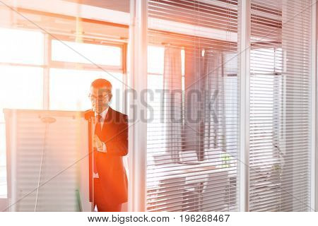Mature businessman writing on whiteboard in board room at office