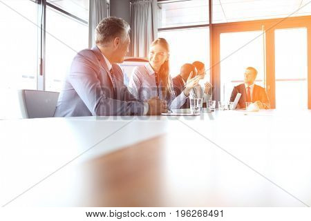 Young businesswoman talking with male colleague in meeting room