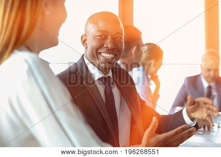 Smiling young businessman discussing with female colleague in board room