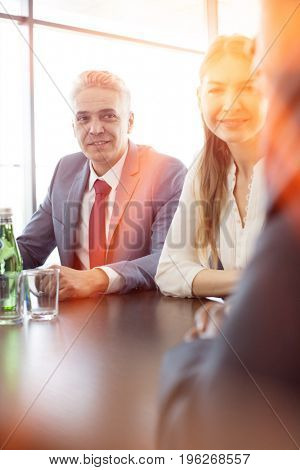 Mature businessman with colleagues at conference table in office