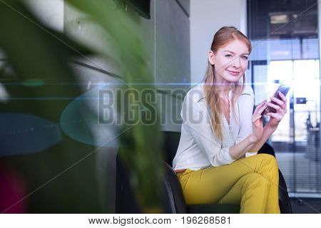 Portrait of smiling young businesswoman using mobile phone on chair in office