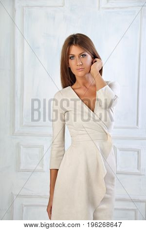 Beautiful Woman With Long Hair Standing And Posing In Fashion White Dress On Light Wall Background I