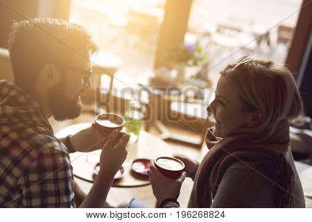 Young couple in love sitting in a cafe drinking coffee having a conversation and enjoying the time spent with each other