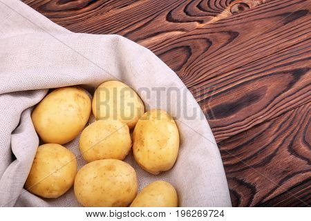 A large pile of raw, fresh and young potatoes on a gray fabric and on a wooden background. Tasty, natural and organic vegetables full of nutritious vitamins.