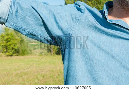 Summer heat concept with male underarm in closeup with stain of sweat on shirt