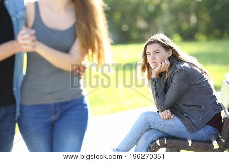 Single envious girl sitting on a bench and seeing an affectionate couple who is walking in a park