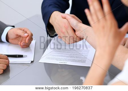 Businessman and business woman shaking hands to each other above signed contract.