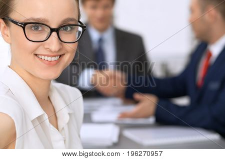 Portrait of a young business woman against a group of business people at a meeting