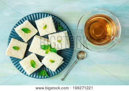 An overhead photo of a plate of cucumber sandwiches, shot from above on a teal blue texture with a cup of tea and a place for text