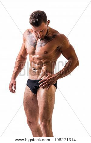 Handsome shirtless muscular man, standing, in studio shot, looking down, isolated on white