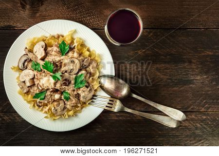 Mushroom beef stroganoff, served with the typical egg pasta, with cremini and champignons, with a glass of red wine, a fork, and a spoon, shot from above on a dark rustic texture with a place for text