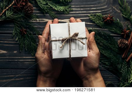 Hands Holding Christmas Simple Present Box And Giving On Stylish Rustic Flat Lay Wooden Background W