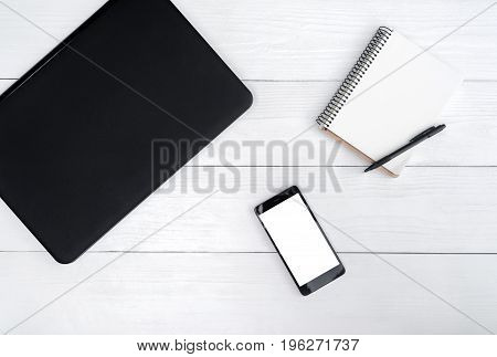 Top View On White Wooden Table With Laptop Computer, Cell Phone, And Empty Diary With Pen, Free Spac