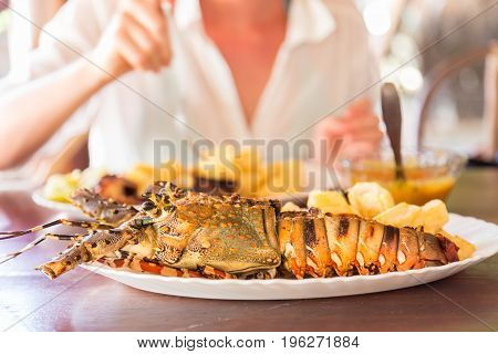 Lady on tropical vacations eating grilled lobster served with potatoes and coconut sauce.