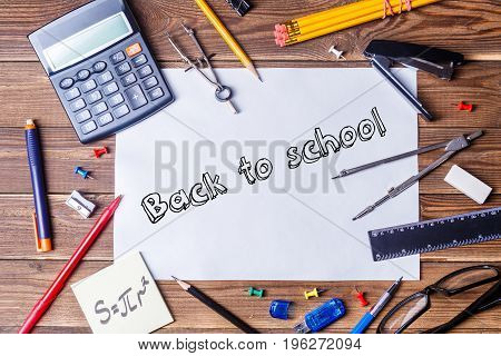 Album sheet with text - back to school and student material on wooden table. Top view