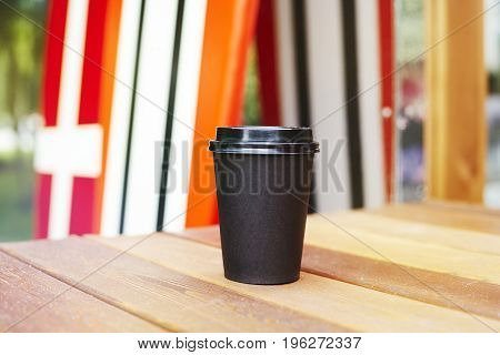 Black paper cup of coffee to takeaway on wooden floor outside the cafe. Surfing boards stand behind at the background
