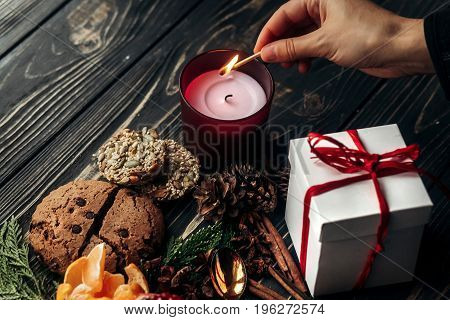 Hand Lighting Up Candle And Present Gingerbread Cookies Garnet Oranges And Spices On Fir Branches On