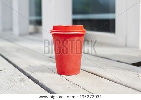 red paper cup of coffee to takeaway on wooden floor outside the cafe. Breakfast morning on air