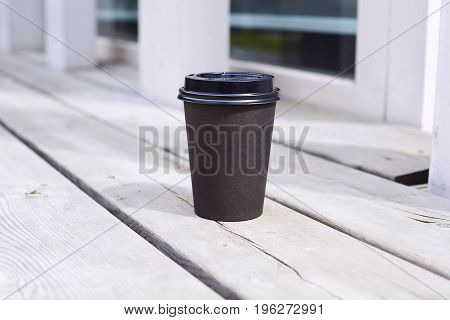 black paper cup of coffee to takeaway on wooden floor outside the cafe. Breakfast morning on air