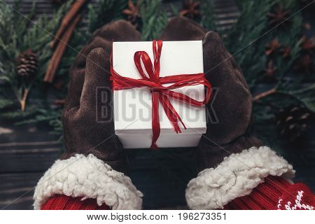 Stylish Christmas Seasonal Greetings Concept. Hands In Gloves Giving Christmas Present With Red Bow
