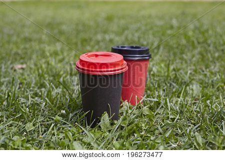 Black and red paper cups of coffee to takeaway on green grass lawn. Breakfast morning outside the cafe