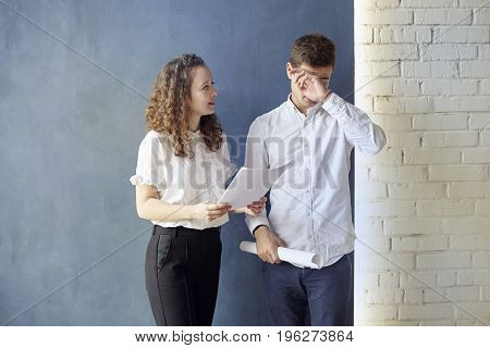 Two young professionals or students woman man talking solving case problem business meeting. Facepalm or upset mood. Office blue wall background