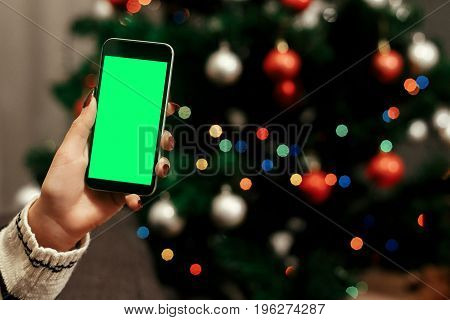 Woman Holding Smartphone With Empty Screen In Front Of Decorated Christmas Tree, Colorful  Lights, R