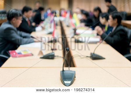 Microphone with blurred photo of conference hall or seminar room with attendee background Business meeting concept.