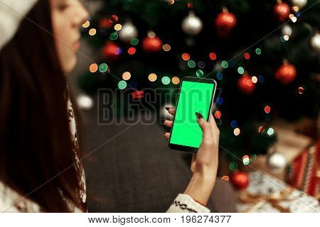 Christmas Advertising Concept With Space For Text. Woman In White Sweater Holding Smartphone With Em