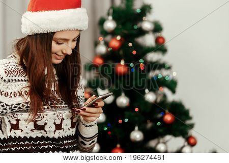 Stylish Woman Holding Phone Looking At Screen At Christmas Tree Lights. Wearing Sweater Reindeers An