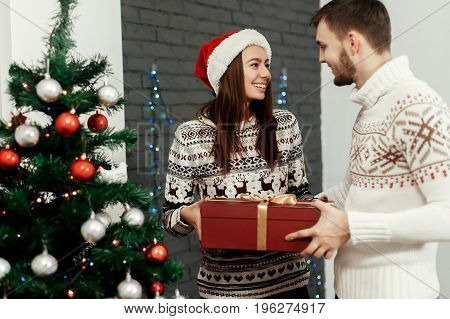 Handsome Man Giving Christmas Present To His Beautiful Woman In Red Santa Hat Near Decorated Christm