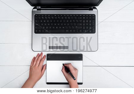 Top View Of Girl's Hands With Graphic Tablet Drawing And Retouching Image On Laptop Computer, Using