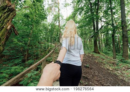 Back view of beautiful young blonde woman in white shirt holding boyfriend's hand outdoors. Girl holding man by hand and leading him to the forest. Follow me. Travel concept