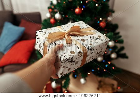 Woman Giving Christmas Present In White Packaging Paper With Snowflakes Wrapped With Yellow Ribbon A