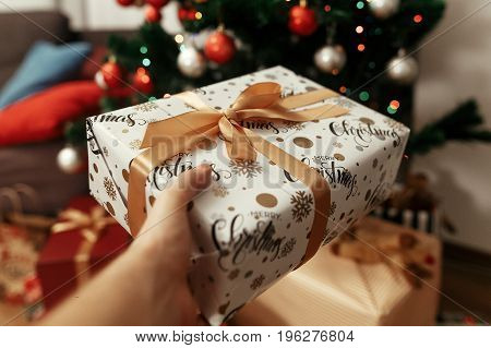 Hand Holding Stylish Christmas Present On Background Of  Tree And Lights. Giving Box. Gift Ideas. Se