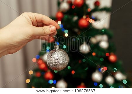 Hand Holding Silver Ball Ornament Close Up Decorating Christmas Tree At Home On Background Of Holida
