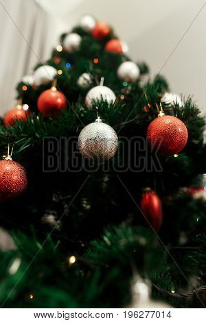Close-up Of Colorful, Red And Silver Christmas Ornaments On Christmas Tree With Lights, Holiday Gree