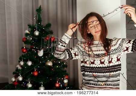 Beautiful Sensual Brunette Woman In White Reindeer Sweater Holding Colorful Lights Near Decorated Ch