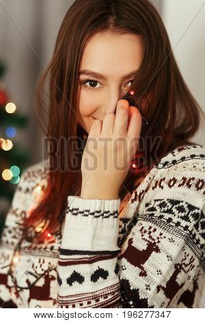 Stylish Woman In Christmas Lights Posing And Smiling At Christmas Tree In Festive Holiday Time. Joyf