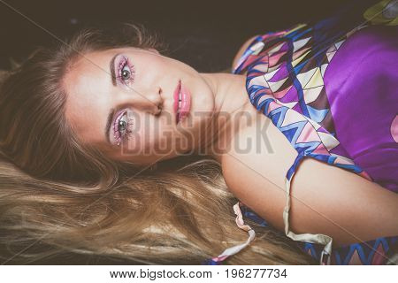 young blonde woman beauty portrait with unusual makeup with crystals lie down studio shot