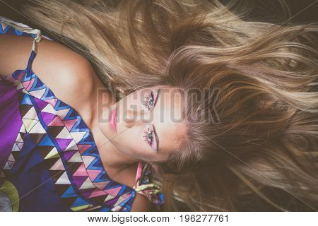 young blonde beauty portrait with crystals makeup  lie down studio shot