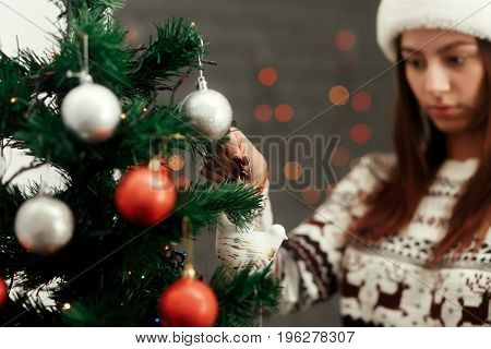 Stylish Woman Decorating Christmas Tree With Red And Silver Ornaments. Wearing Sweater With Reindeer