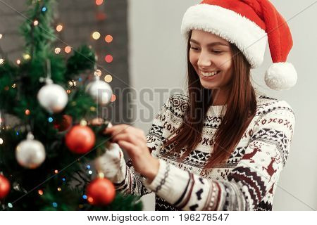 Happy Woman Decorating Christmas Tree. Wearing Sweater Reindeers And Santa Hat Smiling On Background