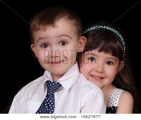 Adorable Young Brother And Sister Embracing. Isolated On Black