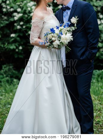 Bride And Groom Embracing In Park Near Jasmine Bush. Groom Hug The Bride In Wedding Dress With Weddi