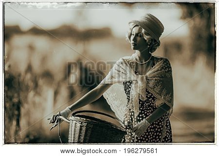 Classic Black And White Photo Of Woman Dressed In 1930S Fashion Standing With Bicycle In Rural Lands