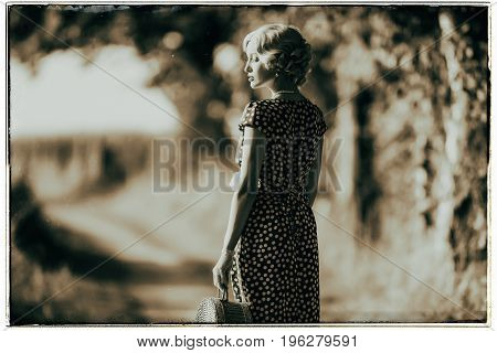 Classic Black And White Photo Of 1930S Fashion Woman Standing With Handbag On Rural Pathway.